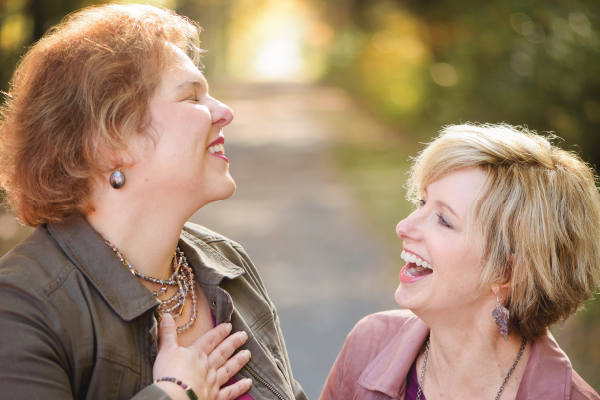 Image of Stacey laughing with a female client and holding her hand to her heart